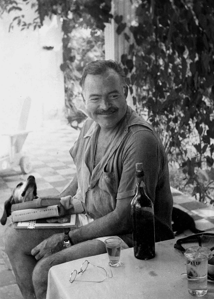"EH 4449P Ernest Hemingway reading books with his dog Negrita at Finca Vigia in Cuba.  Please credit ""Ernest Hemingway Collection/John F. Kennedy Presidential Library and Museum, Boston"""